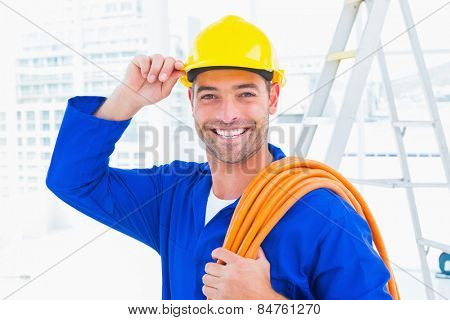 Portrait of confident repairman wearing hard hat while holding wire roll in bright office