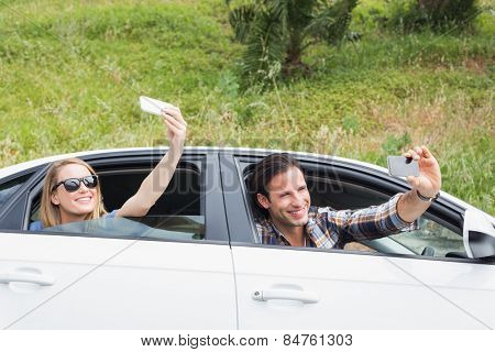 Couple taking selfies in their car