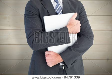 Businessman holding his laptop tightly against bleached wooden planks background