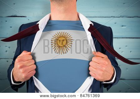 Businessman opening shirt to reveal argentina flag against painted blue wooden planks