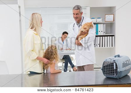 Veterinarian holding cat with its owners in medical office