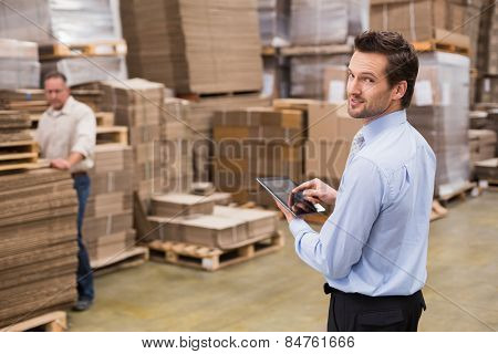 Warehouse manager working on tablet pc in a large warehouse