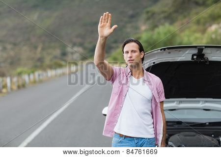 Man waving after a breakdown at the side of the road