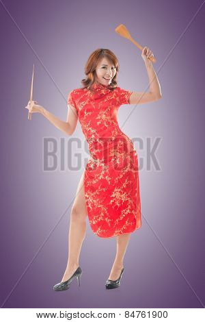 Smiling Chinese woman dress traditional cheongsam standing and holding chopsticks at New Year, full length portrait isolated.