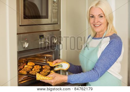 Woman taking tray of fresh cookies out of oven at home in the kitchen