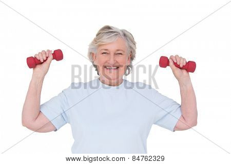 Senior woman lifting hand weights on white background