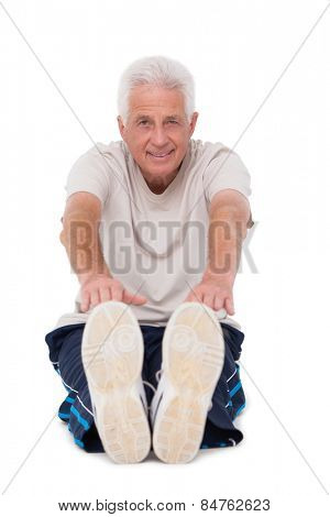 Senior man touching his toes on white background