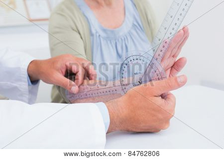 Cropped image of physiotherapist examining female patients wrist with goniometer in clinic