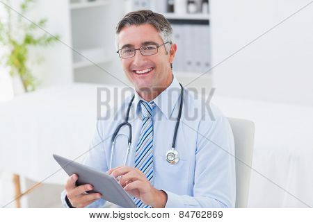 Portrait of happy male doctor using tablet computer in clinic