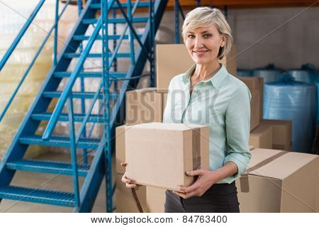 Smiling warehouse manager holding cardboard box in a large warehouse