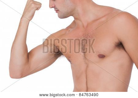 Fit shirtless man flexing his bicep on white background