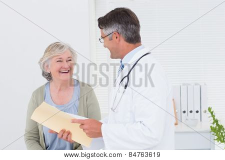 Male doctor and female patient conversing over reports in clinic