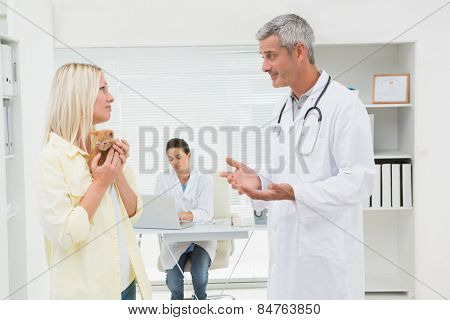 Veterinarian explaining things at cat owner in medical office