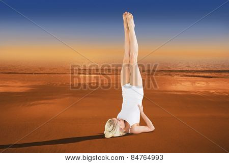 Fit young woman doing the shoulder stand pose against hazy blue sky
