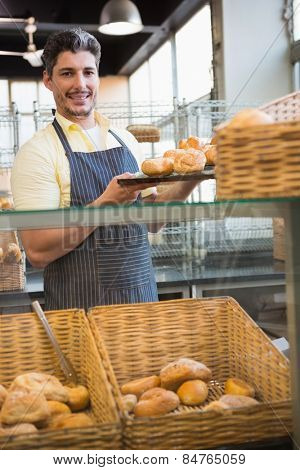 Smiling waiter showing tray of breads at the bakery