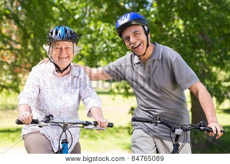 Happy senior couple on their bike on a sunny day