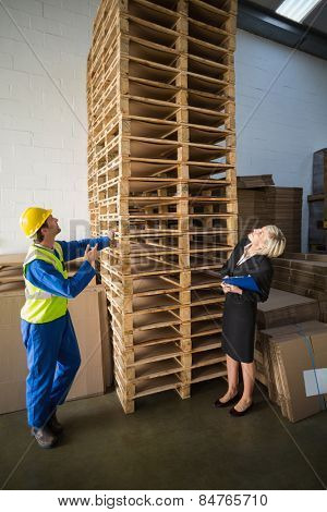 Warehouse worker and his manager looking stack of pallet in a large warehouse