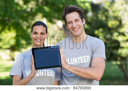 Happy volunteer couple holding tablet pc on a sunny day
