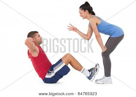 Trainer counting man doing sit ups on white background