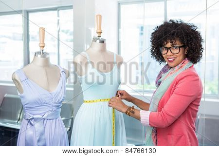 Portrait of female fashion designer measuring dummy waist