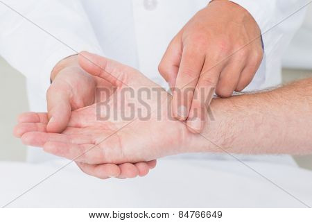 Cropped image of male doctor checking patients pulse rate in clinic