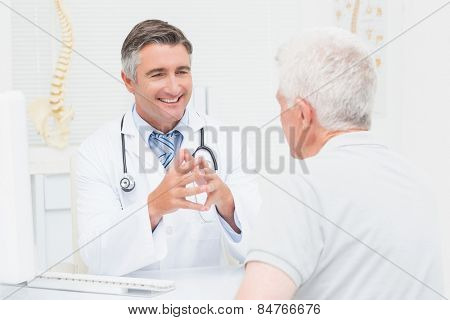 Male orthopedic doctor discussing with senior patient in clinic