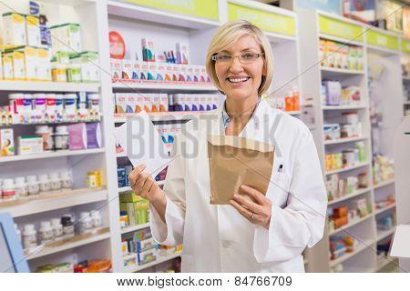 Smiling pharmacist holding prescription and envelope in the pharmacy