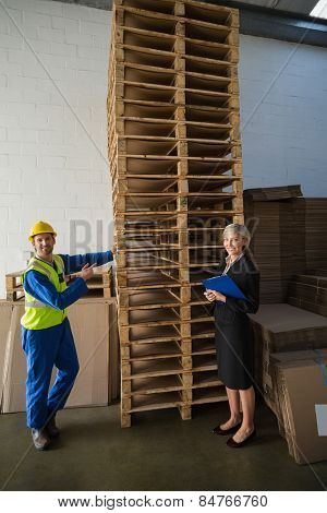 Worker and his manager in front of a stack of pallet in a large warehouse