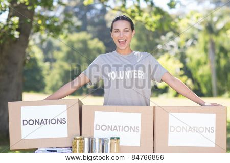 Pretty volunteer with donation boxes in park on a sunny day