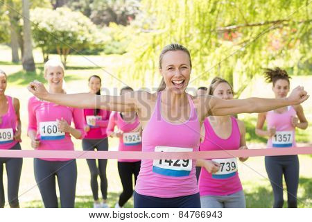 Smiling women running for breast cancer awareness on a sunny day