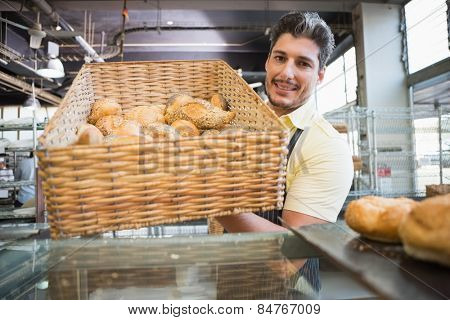 Portrait of waiter in apron showing basket of bread at the bakery