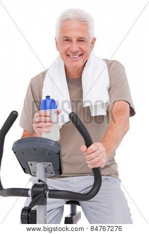 Senior man on exercise bike on white background