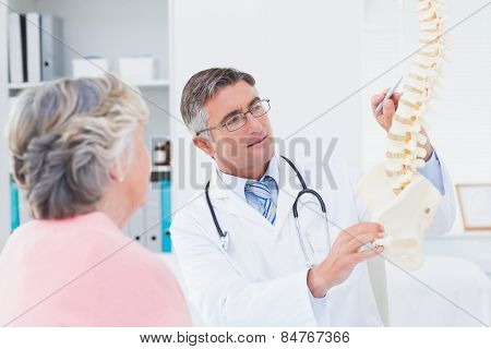 Male doctor explaning anatomical spine to senior woman in clinic