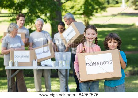 Happy siblings holding donation box on a sunny day