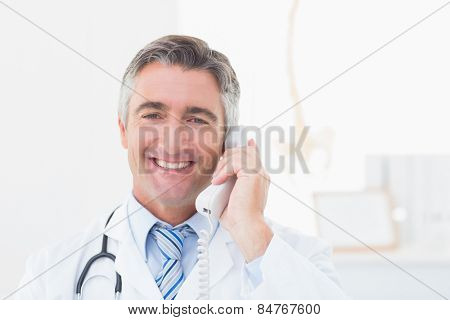 Portrait of happy doctor using landline phone in clinic