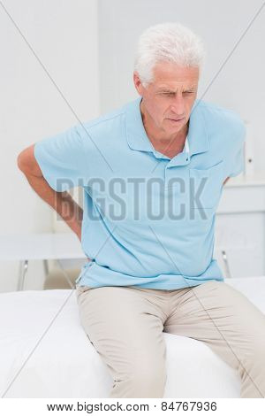 Senior male patient suffering from backache in clinic