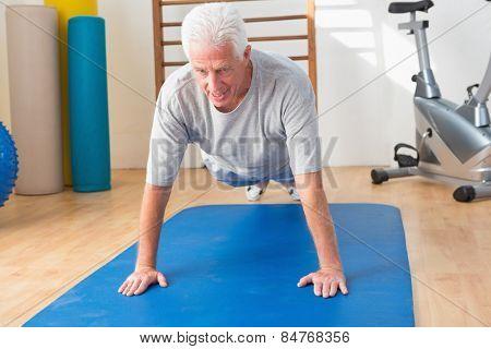 Senior man in plank position in fitness studio