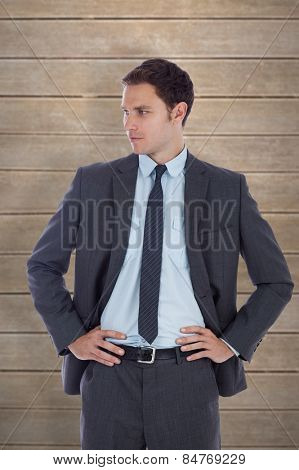 Serious businessman with hands on hips against wooden planks