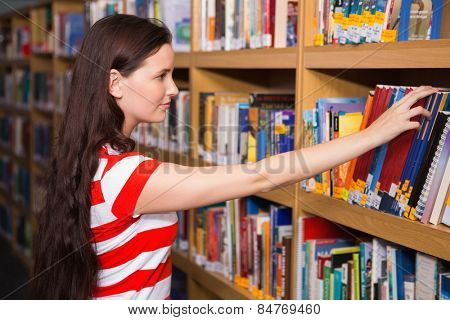 Pretty student taking book from shelf in library at the university