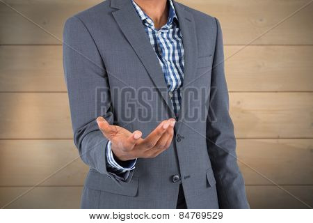 Businessman holding hand out against bleached wooden planks background