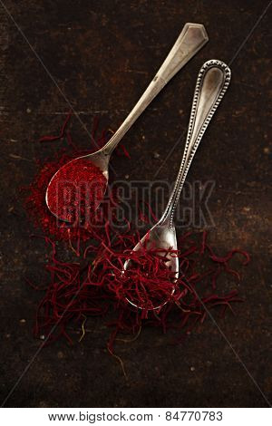 saffron spice threads and powder  in vintage  old spoons,  old metal background, closeup