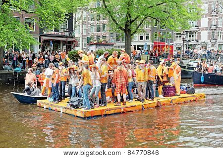 AMSTERDAM - APRIL 26: Canals of Amsterdam full of people in orange on boats during the celebration of kings day on April 26, 2014 in Amsterdam, The Netherlands