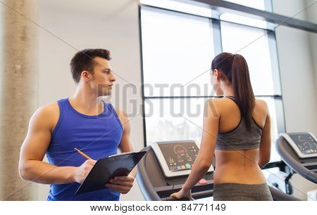 sport, fitness, lifestyle, technology and people concept - woman and trainer with clipboard working out on treadmill in gym