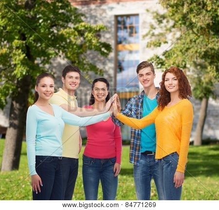 friendship, education, teamwork, gesture and people concept - group of smiling teenagers making high five over campus background