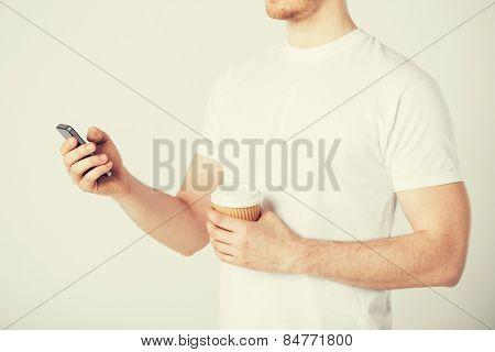 man with smartphone and take away coffee cup