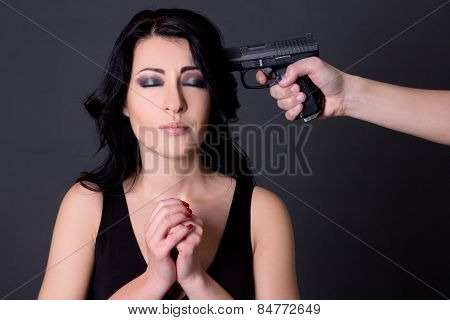 Violence - Young Beautiful Woman Hostage And Male Hand With Gun Over Grey
