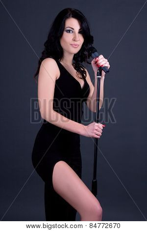 Young Beautiful Sexy Woman Singer With Microphone Over Grey