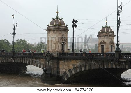 PRAGUE, CZECH REPUBLIC - JUNE 3, 2013: People observe the rising water from the Legion Bridge partially flooded by the swollen Vltava River in Prague, Czech Republic.