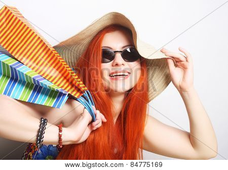 attractive redhair shopping woman wearing sunglasses and hat