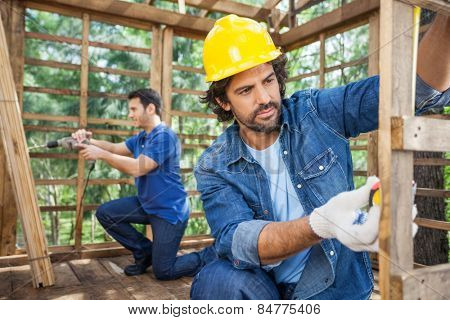 Male construction worker measuring wooden cabin while colleague working in background at site